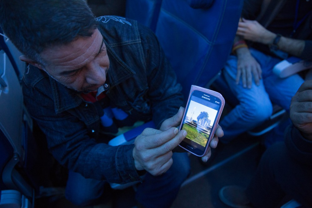 A Syrian refugee shows his home town of Hama on his phone while enroute to Canada. © IOM/Muse Mohammed 2015 (https://www.flickr.com/photos/iom-migration/24366713595)
